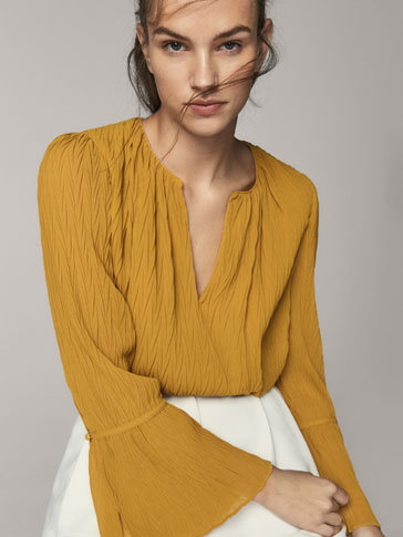 GEOMETRIC PLEATED BLOUSE WITH FLARED DETAIL