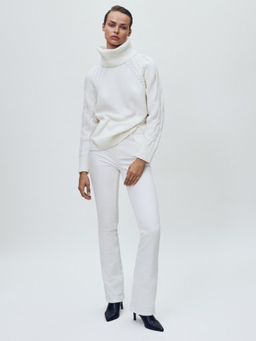 Cape sweater with high neck and cable-knit sleeves
