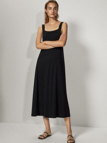 Black dress featuring a square-cut neckline