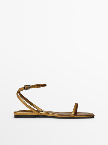 Flat gold leather sandals with crossover straps